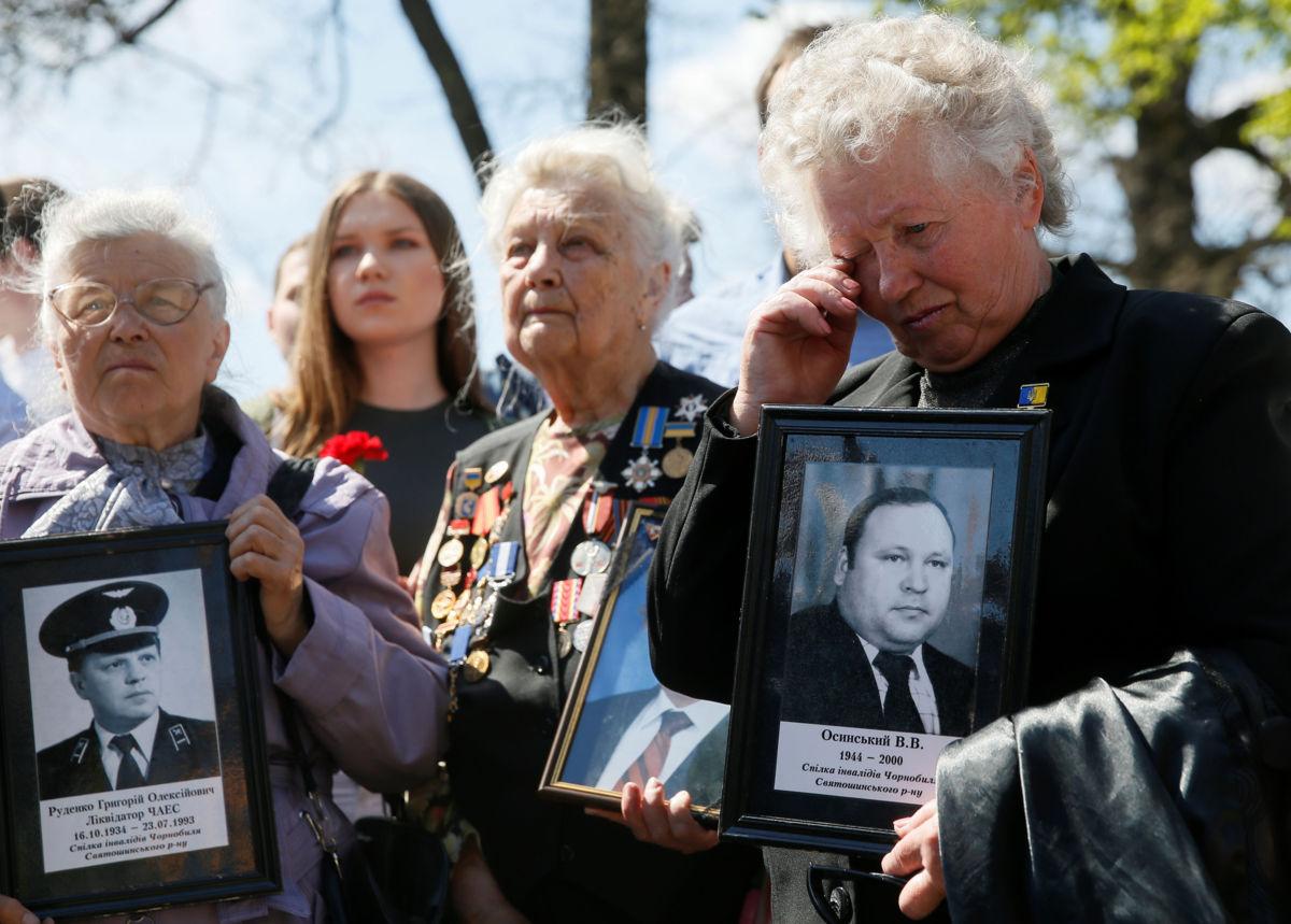 Fotos: Mujeres sostienen retratos de familiares víctimas del desastre nuclear de Chernóbil / Reuters
