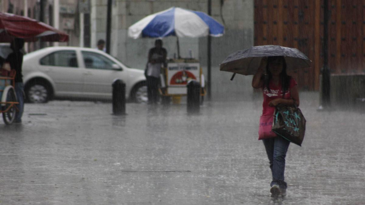 Peatón caminando por las calles de Puebla bajo la lluvia